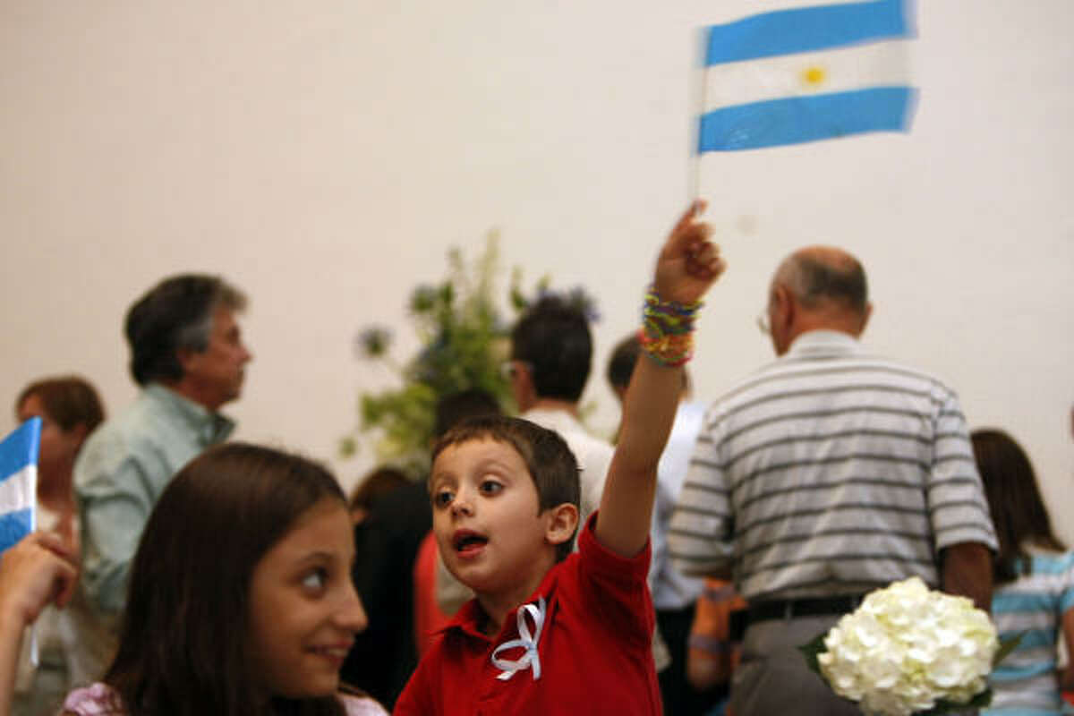 Leandro Bilello, 6, waves an Argentinean flag next to his sister Melian Bilello, 8, as local Argentineans gathered to celebrate Argentina's Independence Day and bicentennial at the Museum of Fine Arts Houston Tuesday, May 25, 2010, in Houston.