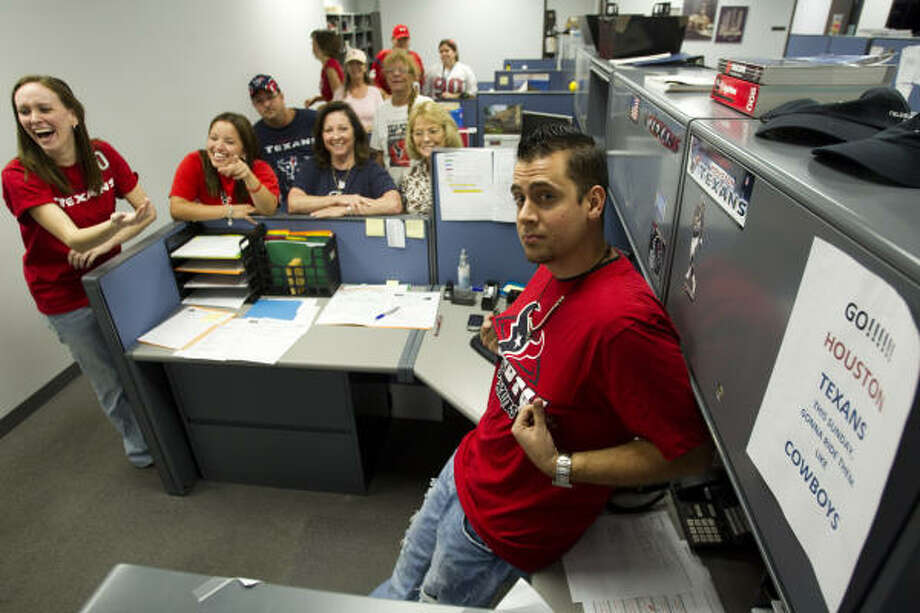 Texans fans fill their side of the office with red and blue at Fielder Electric Supply. Photo: Brett Coomer, Chronicle