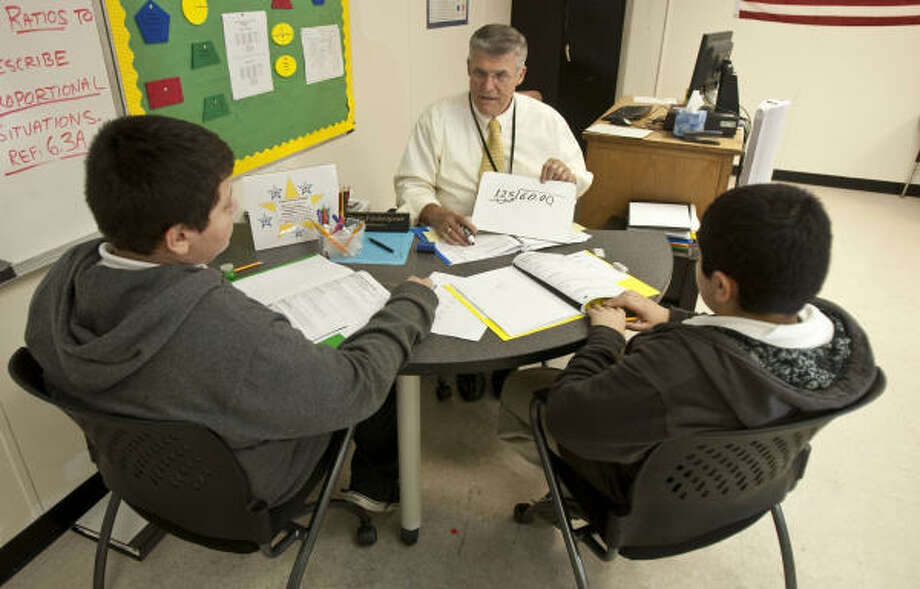 Math tutor David Fashenpour, center, explains a math equation during a lesson with Cristian Garcia, 12, left, Fernando Vera, 11, at Dowling Middle School. Fashenpour is on his third career as a tutor as part of the Apollo 20 program. Photo: James Nielsen, Houston Chronicle