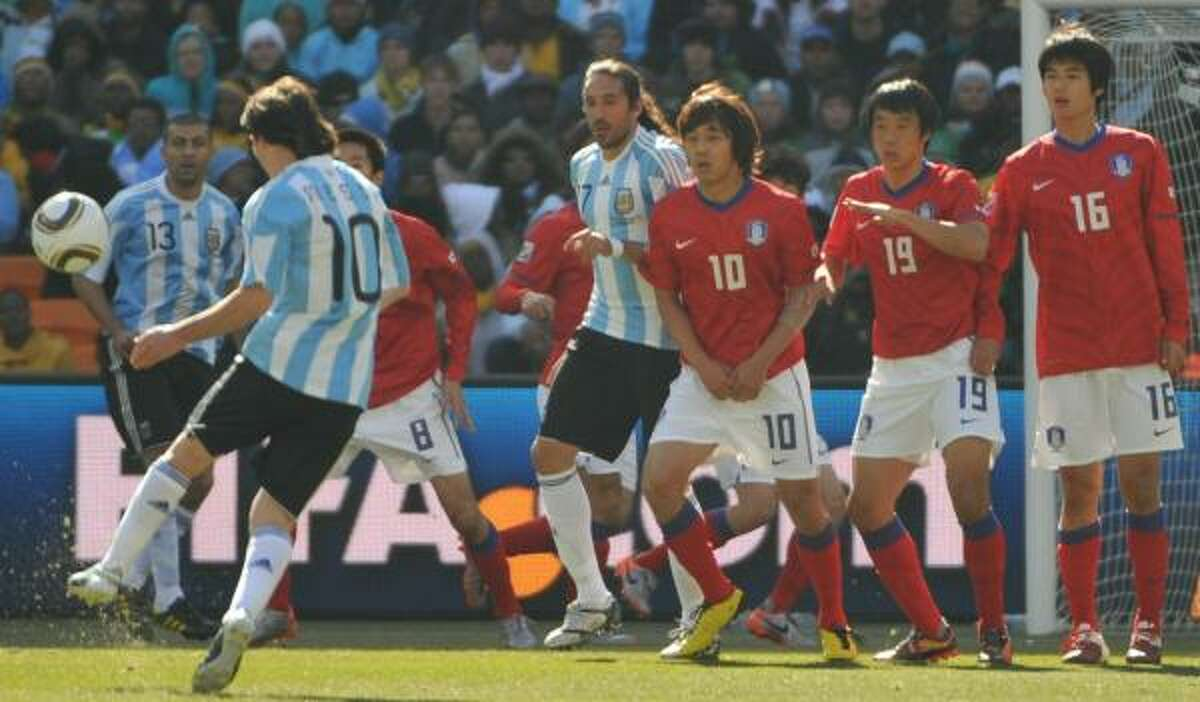 Argentina's Lionel Messi takes a free kick which was deflected off of South Korea striker Park Chu-Young (unseen) and resulted in Argentina's first goal.