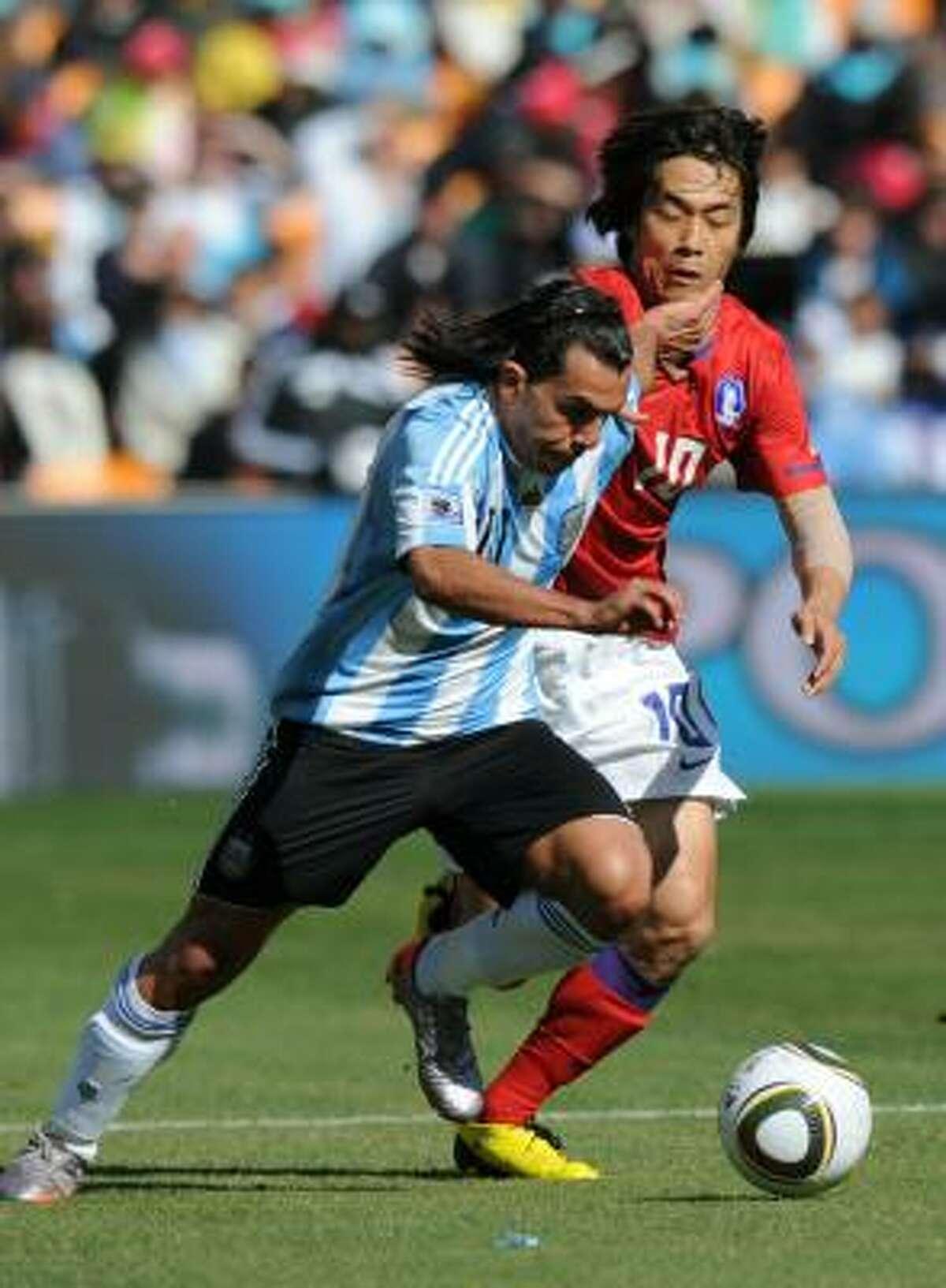 Carlos Tévez (izq.) se escapa con el balón de la marca de Park Chu-Young.