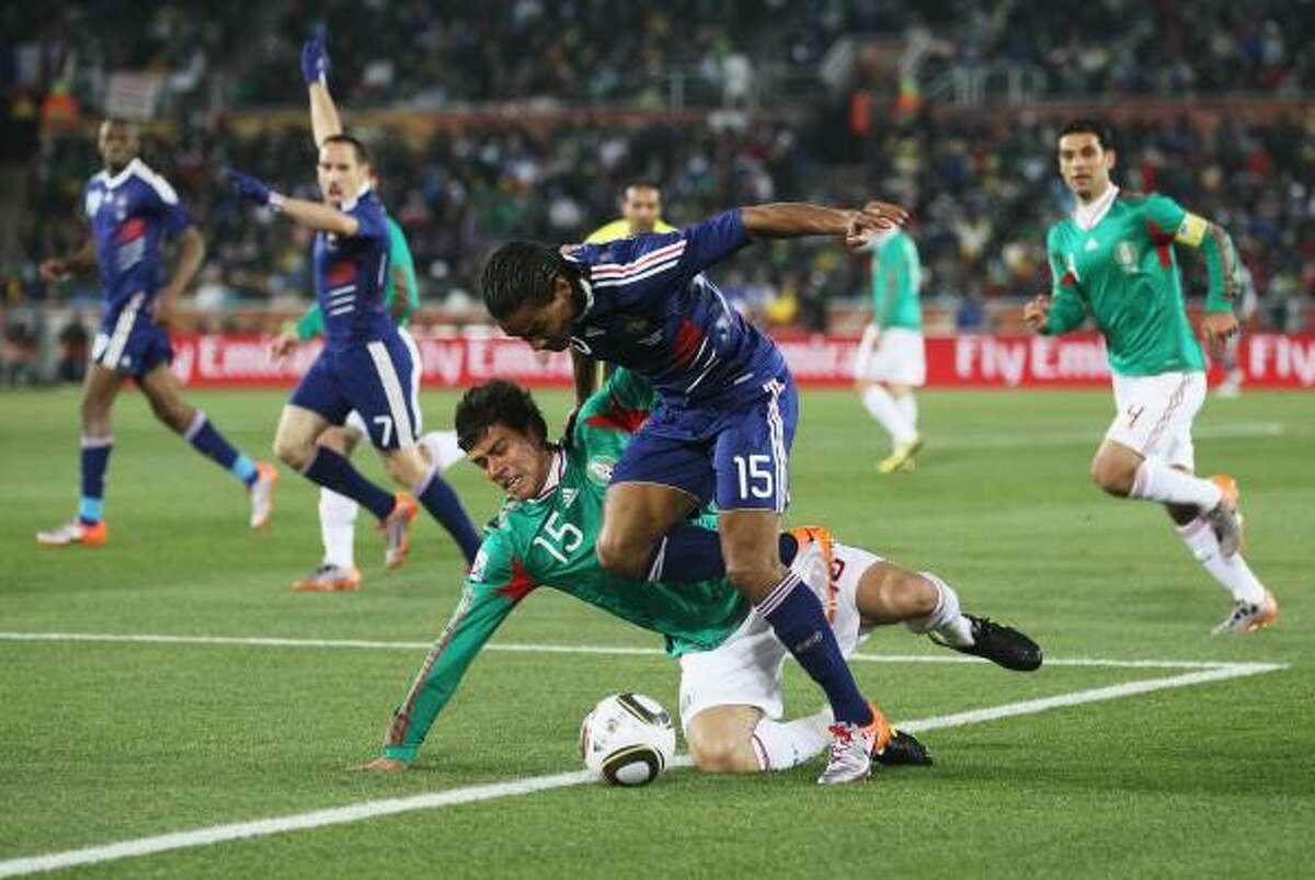 El mexicano Héctor Moreno (izq.) trata de robarle la pelota, con falta, al francés Florent Malouda.