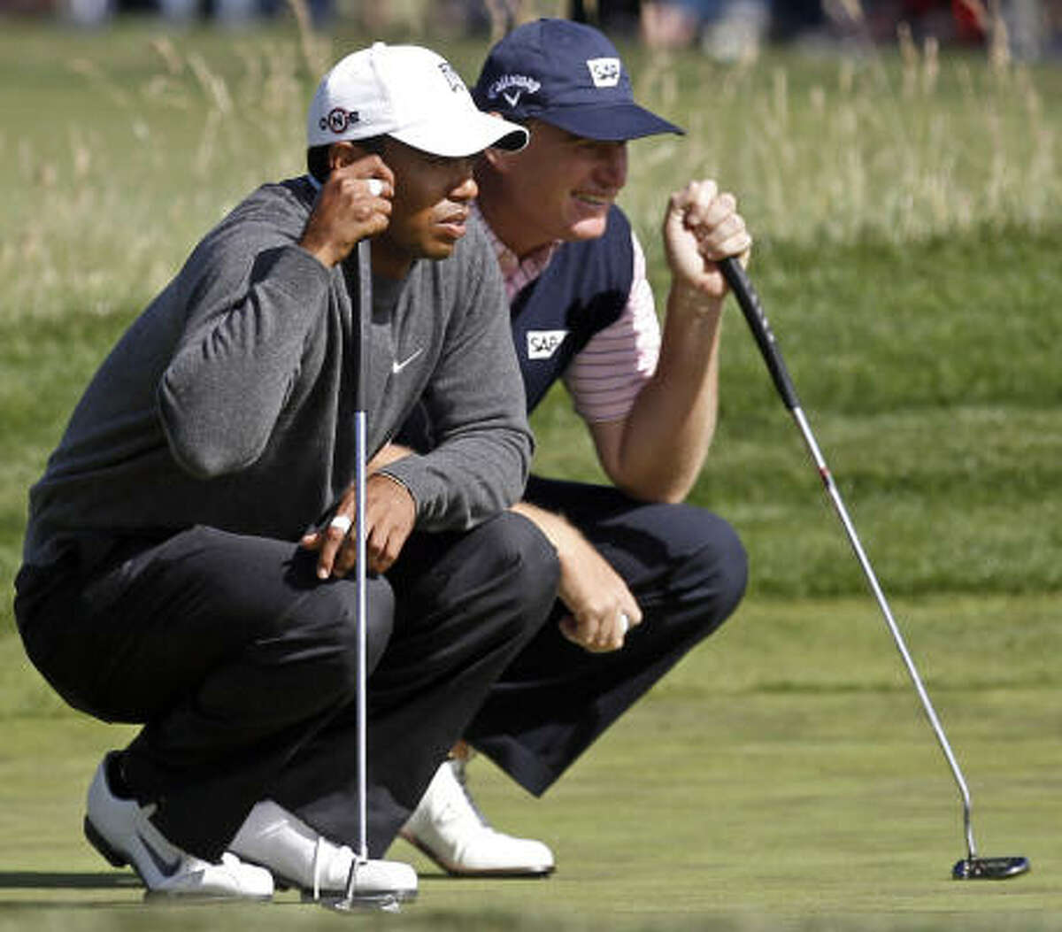 Tiger Woods, left, and Ernie Els of South Africa line up putts on the 12th hole during the first round.