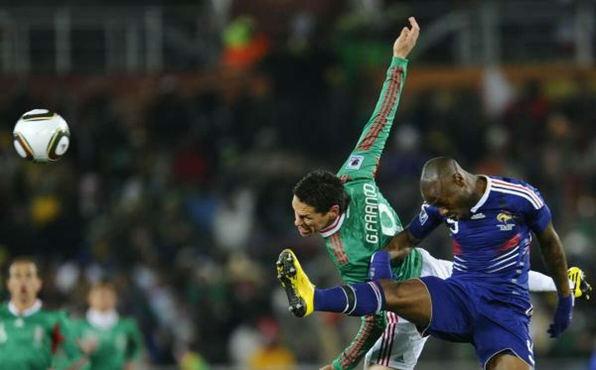 Mexico's Guillermo Franco tries to get a head on the ball as France's Djibril Cisse defends.
