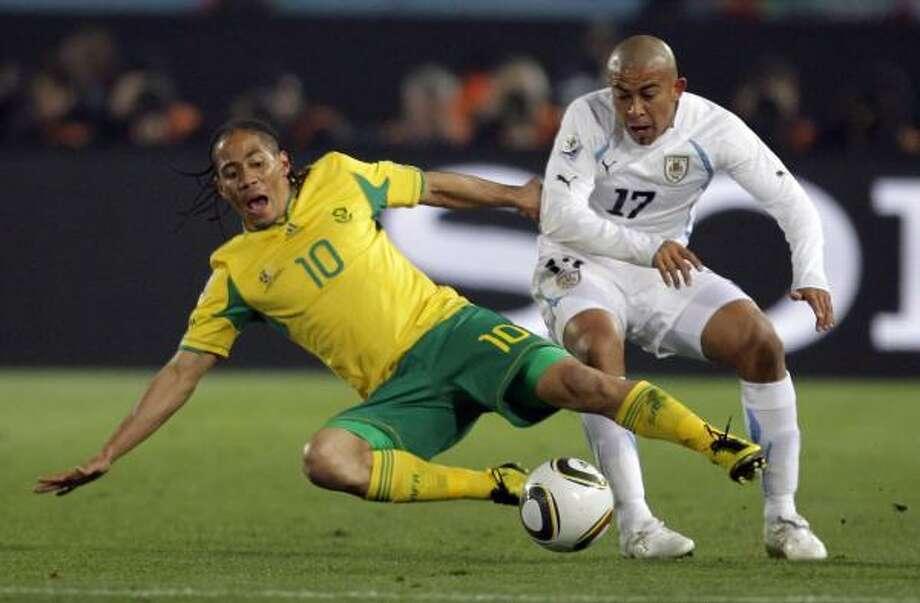 El sudafricano Steven Pienaar (izq.) se barre ante el jugador uruguayo Edigio Arévalo Ríos. Photo: Matt Dunham, AP