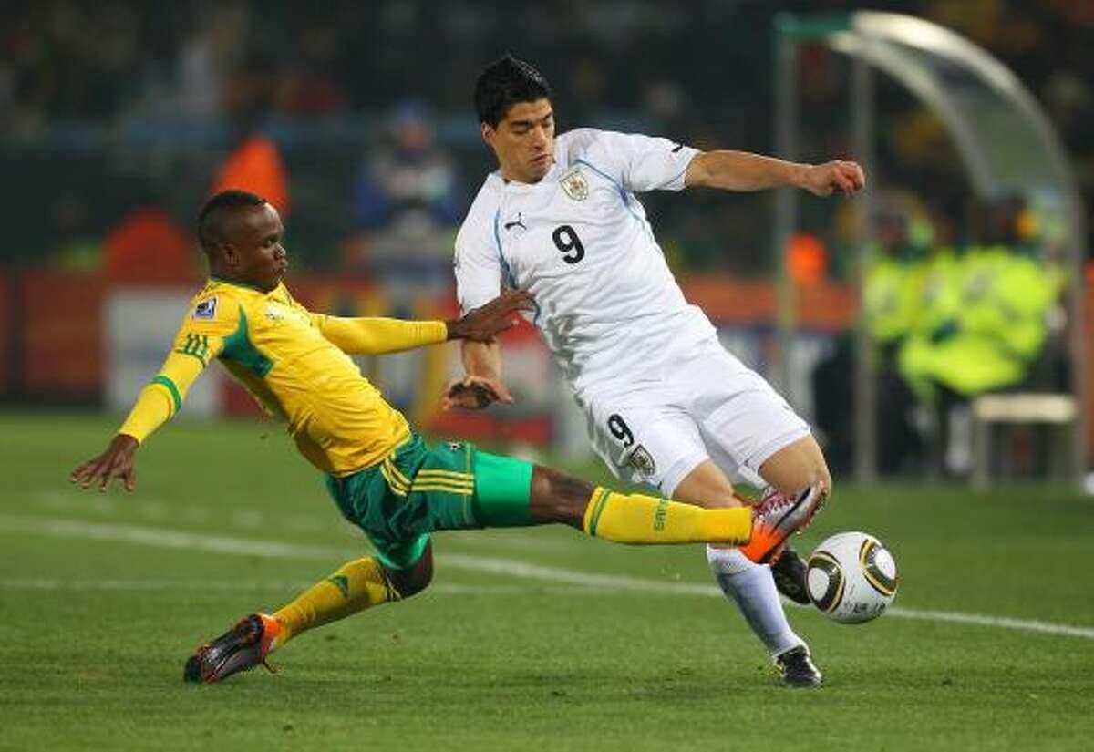 El sudafricano Siboniso Gaxa (izq.) trata de robarse la pelota al uruguayo Luis Suárez.