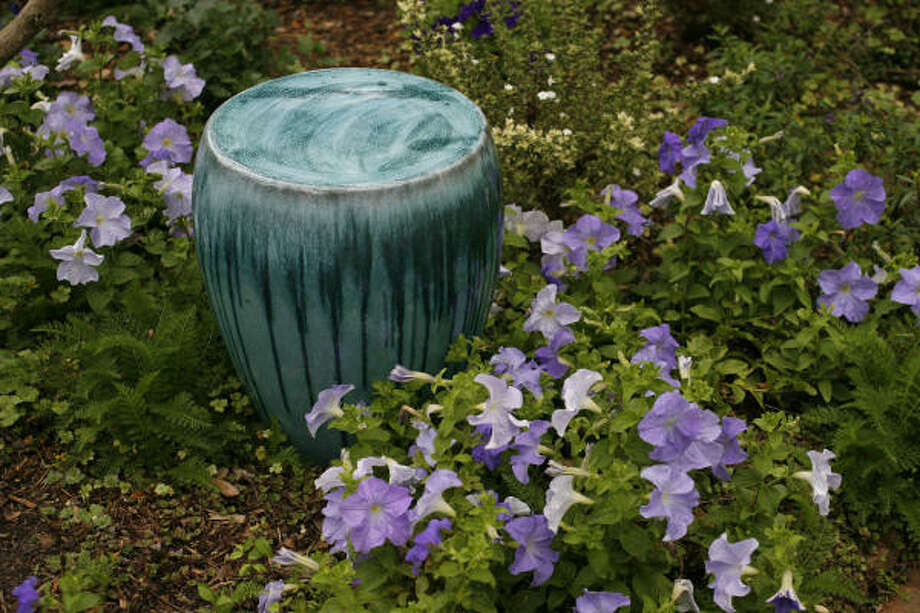 A peaceful picture: A turquoise stool and cool blanket of lavender-colored petunias have a calming influence in the garden. Photo: Sharon Steinmann, Chronicle