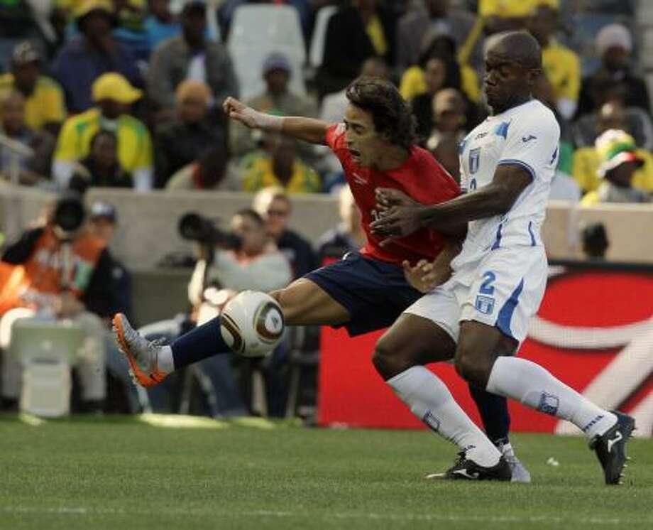 El chileno Jorge Valdivia (der.) se barre para tratar de robarle la pelota al hondureño Osman Chávez. Photo: Claudio Cruz, AP