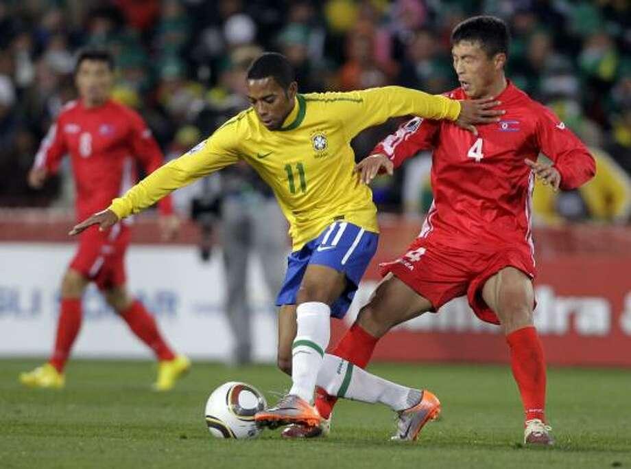 El brasileño Robinho (izq.) se escapa de la marca del norcoreno Pak Nam Chol. Photo: Frank Augstein, AP