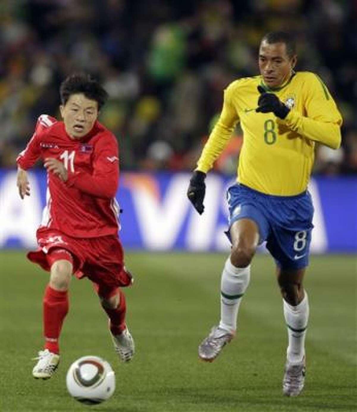 El brasileño Gilberto Silva (der.) corre tras el norcoreano Mun In Guk.
