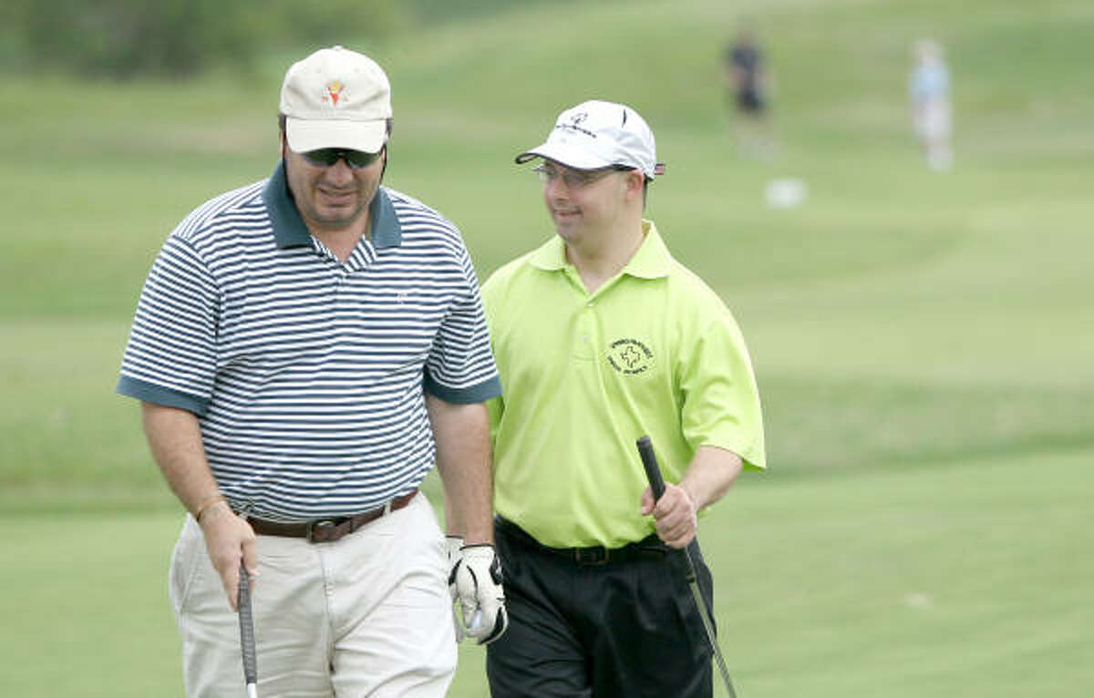 Peter Horton, a unified partner, celebrates a strong finish with Lee Bell of the Spring Panthers Special Olympics golf team during practice.