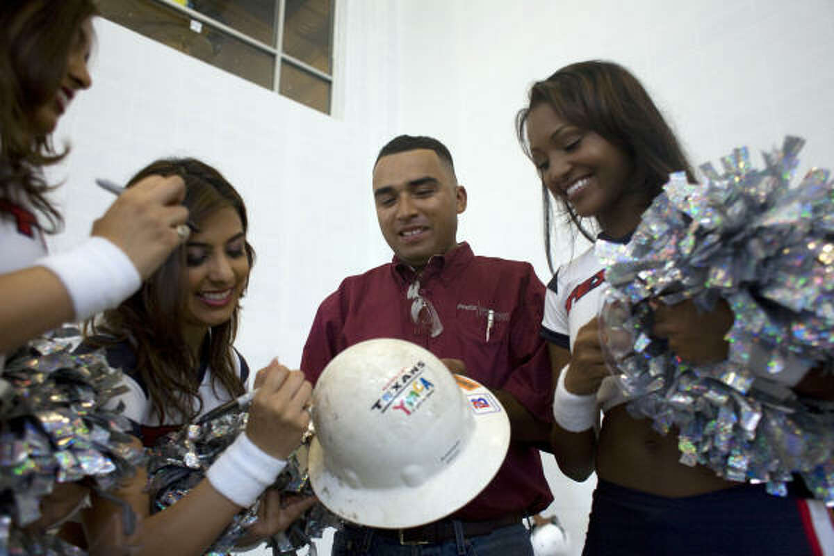 Robert Manriquez with Fretz Construction, one of the workers helping build the new Houston Texans YMCA on the corner of Griggs Rd. and Martin Luther King Blvd., gets his work helmet signed by Houston Texans cheerleaders as construction workers were treated to a free lunch and a visit by Texans owner Bob McNair. The Houston Texans and the Greater Houston YMCA have partnered to open a new YMCA facility in the Palm Center community of Third Ward. The facility, replaces the old South Central YMCA. The new facility is scheduled to open at the end of 2010.