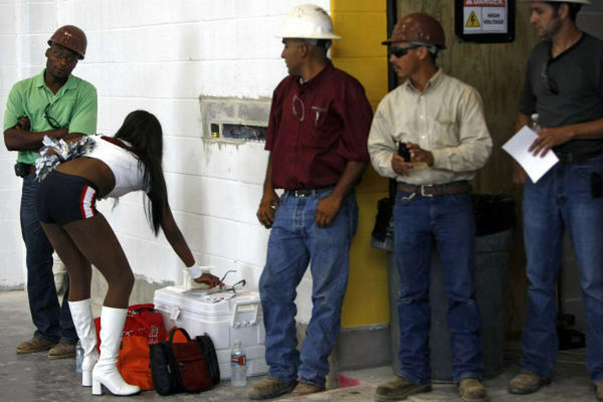 A group of construction workers get a closer look at Houston Texans cheerleader, Savannah, at the under construction Houston Texans YMCA facility on the corner of Griggs Rd. and Martin Luther King Blvd.