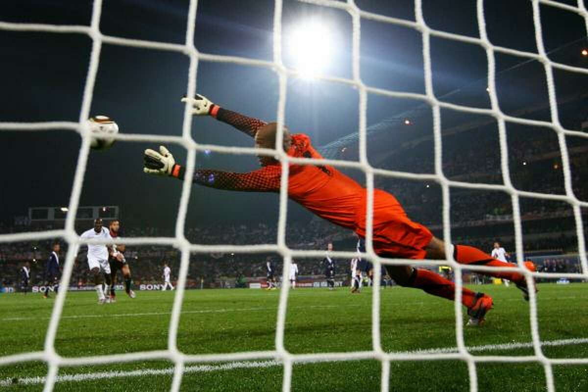 U.S. goalkeeper Tim Howard dives to make a save on a shot from England's Emile Heskey.