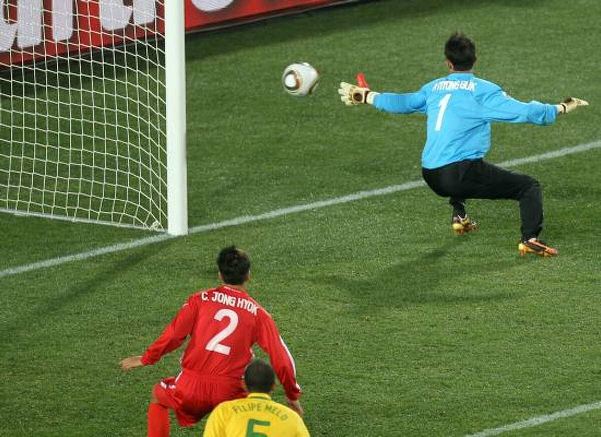 North Korea goalkeeper Ri Myong-Guk is surprised by Maicon's shot.