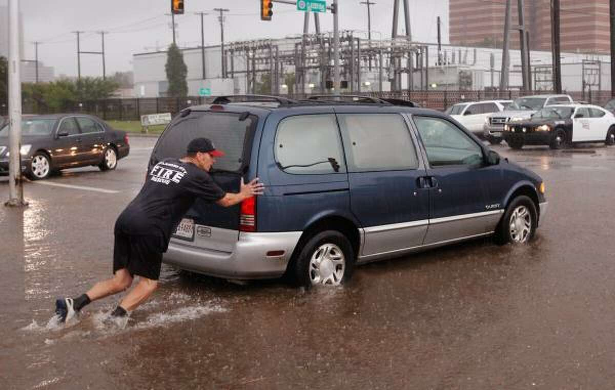 An Oklahoma City firefighter pushes a van that had stalled in high water. Video: Oklahoma rescues.