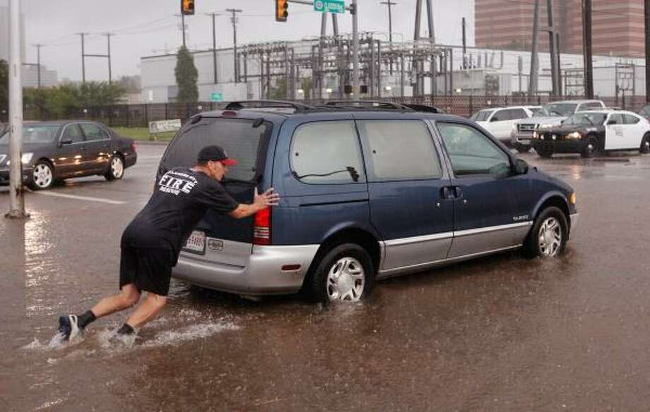 An Oklahoma City firefighter pushes a van that had stalled in high water. Video: Oklahoma rescues. Photo: JIM BECKEL, AP
