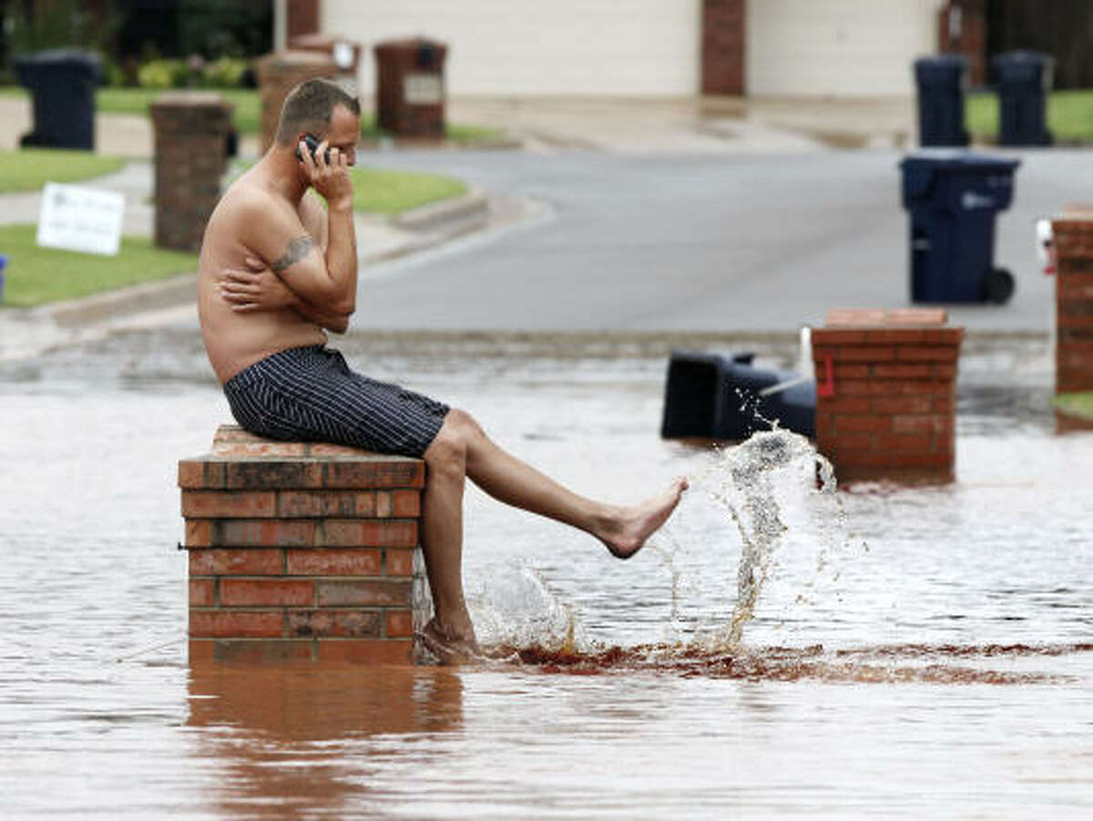 Daniel Parker splashes water while sitting on his mailbox in front of his house in Edmond, Okla. Read the story: Dozens stranded