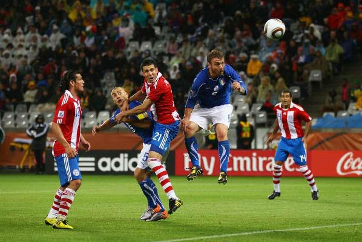 El paraguayo Antolín Alcaraz (21) remata de cabeza para anotar el primer gol ante Italia.