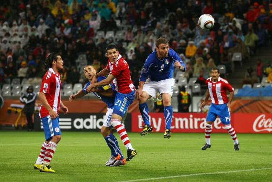 El paraguayo Antolín Alcaraz (21) remata de cabeza para anotar el primer gol ante Italia. Photo: Lars Baron, Getty Images
