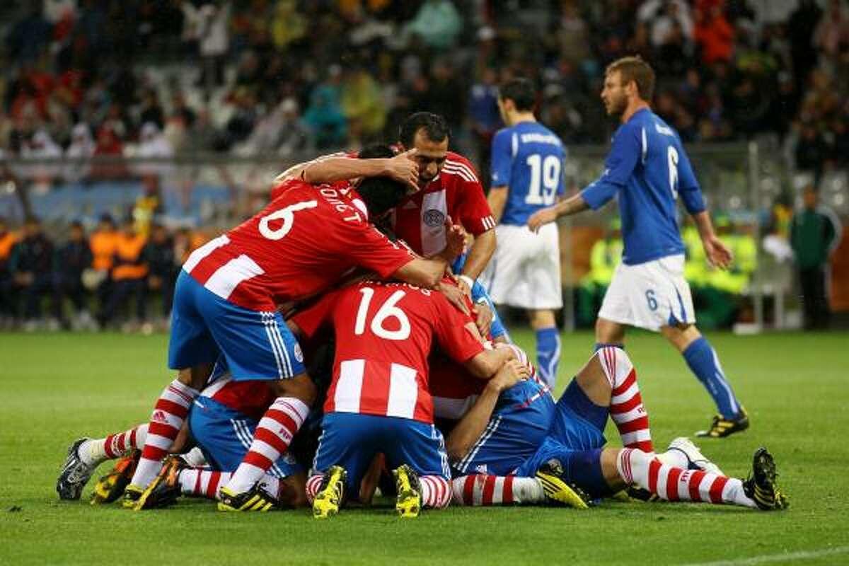 Los jugadores paraguayos abrazan a Alcaraz luego del primer tanto del partido.