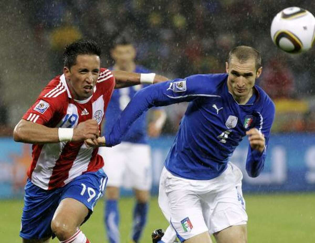 Paraguay's Lucas Barrios, left, fights for the ball against Italy's Giorgio Chiellini.