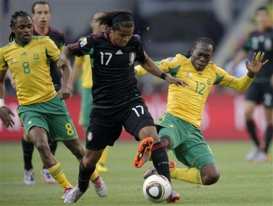 El mexicano Giovanni Dos Santos aguanta la barrida de un jugador sudafricano. Photo: Luca Bruno, AP