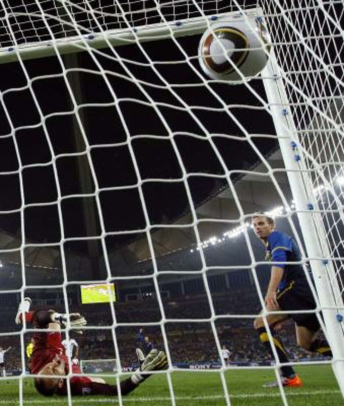The ball hits the back of the net for Lukas Podolski, giving the German side its first goal.