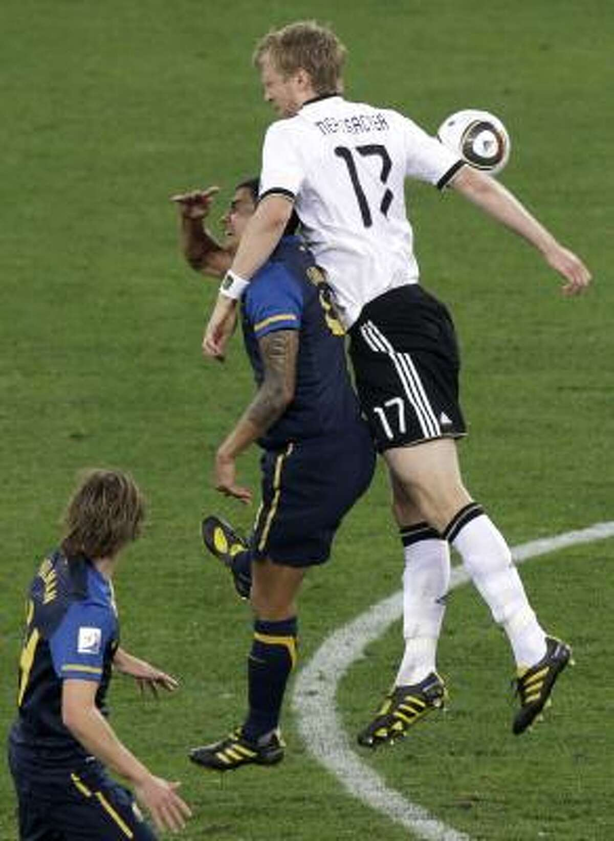 Germany's Per Mertesacker goes over Australia's Tim Cahill in a battle for the ball.