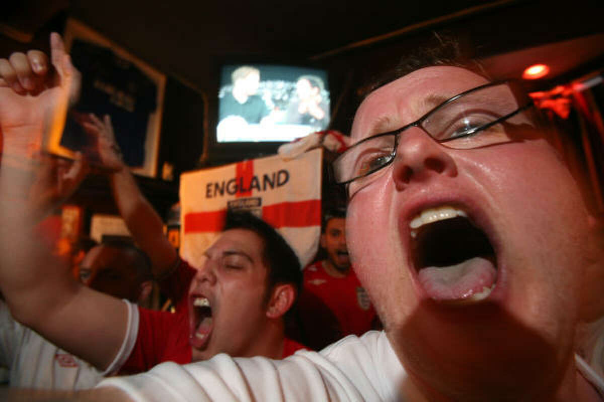 Joshua Back and Jason Yu, both originally from England, and England national soccer team supporters shout soccer chants as hundreds of U.S. and England fans gather at Richmond Arms Pub.