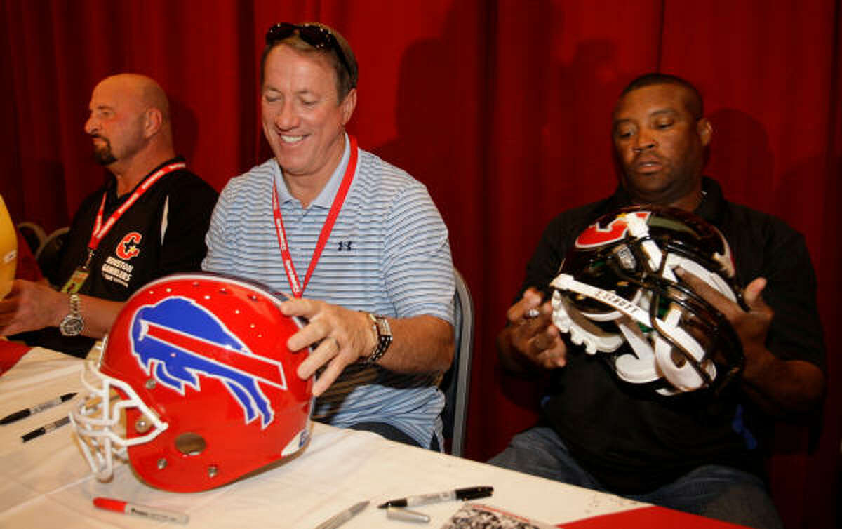 Former Gamblers teammates Scott Boucher (left), Jim Kelly and Ricky Sanders sign autographs during a 25-year reunion in June 2010 in Houston.