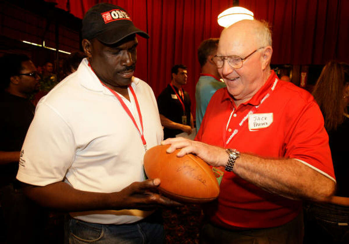 Former Gamblers player Charlie Davis, left, and coach Jack Pardee look over a USFL autographed football, which was put up for auction.