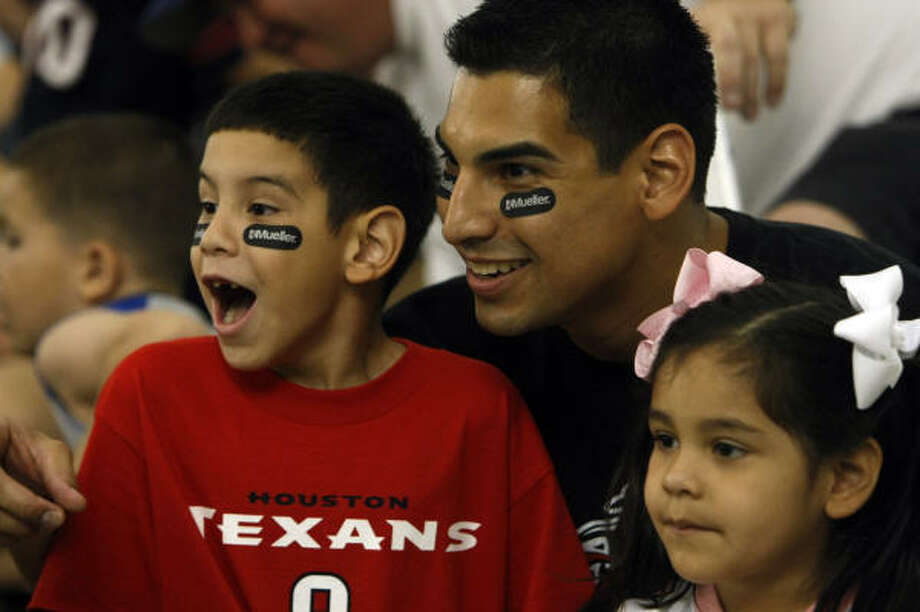 Jacob Saldivar, 4, reacts to seeing the Houston Texans' mascot while with his dad, Joaquin Saldivar, 27, and his sister, Madeline, 4, as the Houston Texans hosted the Second Annual All Pro Dad Father & Kids Experience at the Methodist Training Center in Houston. The Houston Texans' Steve Slaton, Andre Davis, James Case, special teams coach Joe Marciano and former Houston Oiler, Bruce Matthews all gave advice to the fathers and lead football-based activities. Photo: Johnny Hanson, Chronicle