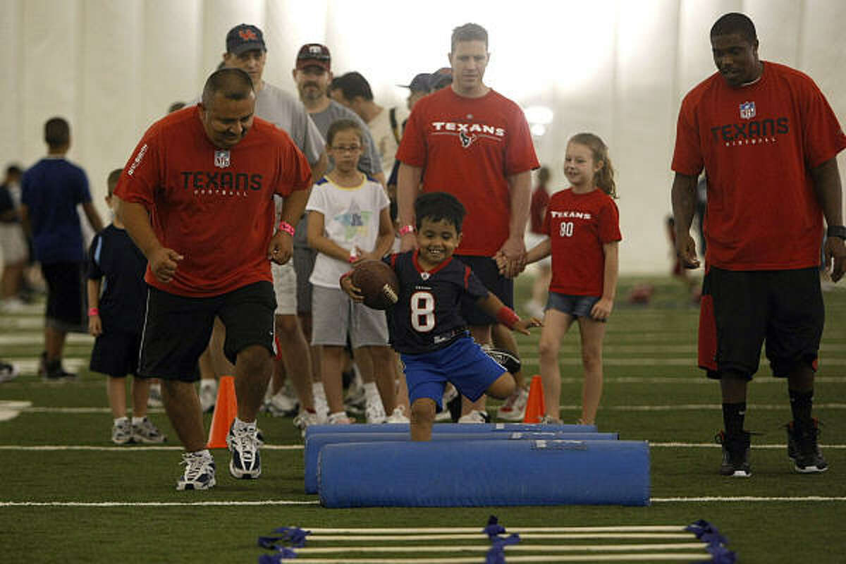 Joshua Lopez, 5, runs over obstacles next to his father, Daniel, 39, and the Houston Texans' Steve Slaton as the Houston Texans hosted the Second Annual All Pro Dad Father & Kids Experience at the Methodist Training Center.