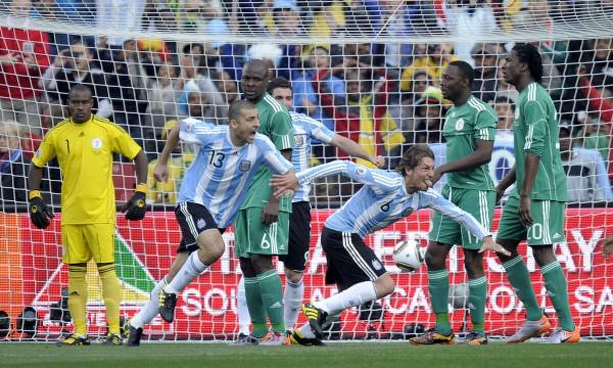 ARGENTINA 1, NIGERIA 0 Argentina's Gabriel Heinze, third right, takes off to celebrate after scoring the only goal of the match. Also, see photos from the U.S.-England match.