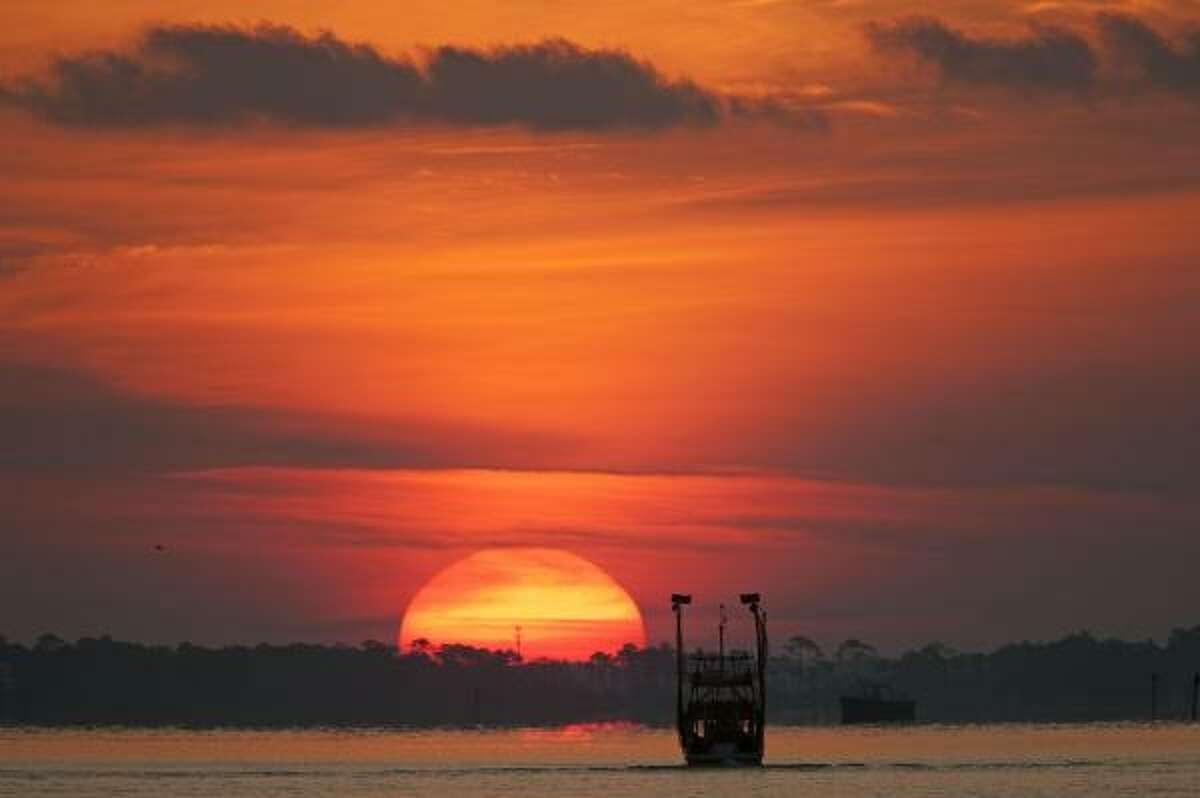 A boat patrols Perdido Bay as the sun rises in Orange Beach, Ala., on Saturday. Authorities closed Perdido Pass to boat traffic amid fears that large amounts of oil would flow into the pass on the tidal change.