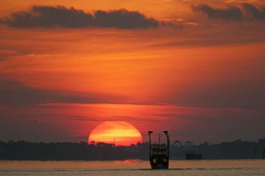 A boat patrols Perdido Bay as the sun rises in Orange Beach, Ala., on Saturday. Authorities closed Perdido Pass to boat traffic amid fears that large amounts of oil would flow into the pass on the tidal change. Photo: Dave Martin, Associated Press