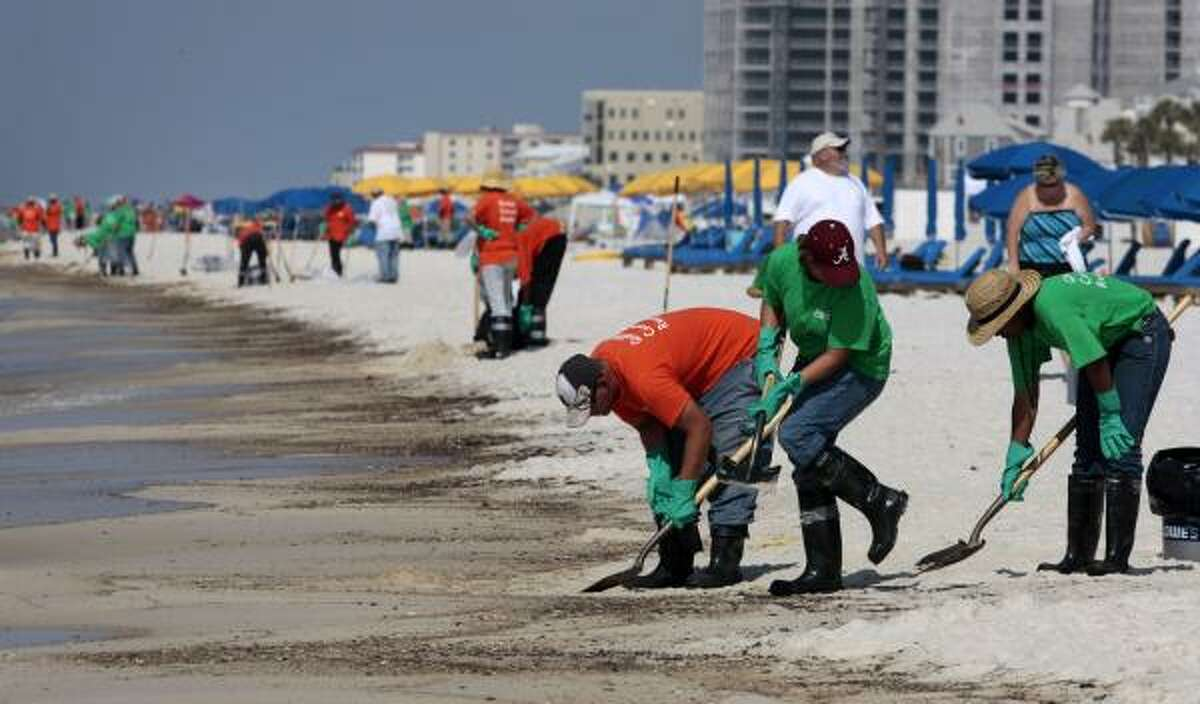 Workers hired by BP make an effort to clean the shore Saturday in Orange Beach, Ala.