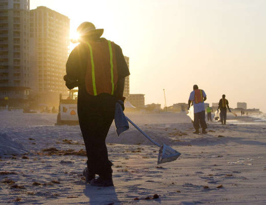 As the sunrises at Pensacola Beach, British Petroleum clean up crews walk along the shore looking for and cleaning up small bits of oil debris from the Deepwater Horizon oil spill in Pensacola, Florida. Photo: Billy Smith II, Chronicle