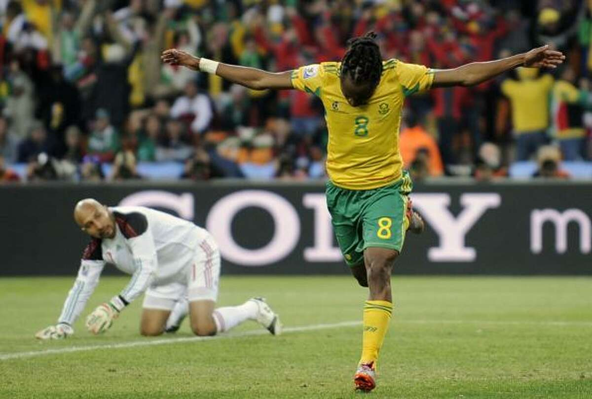 South Africa's Siphiwe Tshabalala, right, celebrates after scoring the opening goal against Mexico goalkeeper Oscar Perez.