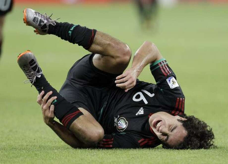 Mexico's Efrain Juarez is on the ground after tripping over South Africa's Tsepo Masilela. Photo: Themba Hadebe, AP