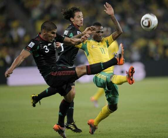 Mexico's Carlos Salcido, left, and Mexico's Andres Guardado, center, clear the ball against South Africa's Teko Modise. Photo: Martin Meissner, AP