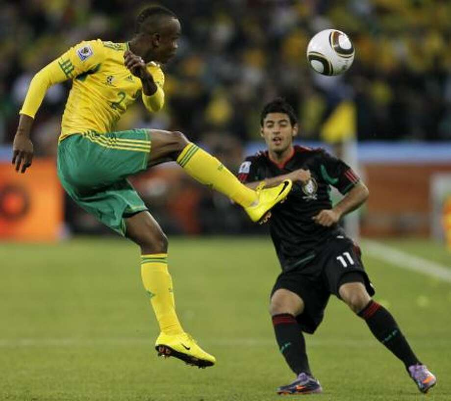 South Africa's Siboniso Gaxa, left, clears in front of Carlos Vela. Photo: Matt Dunham, AP