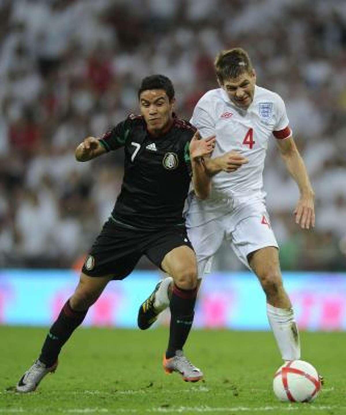 Steven Gerrard (der.) y Pablo Barrera luchan por el balón.