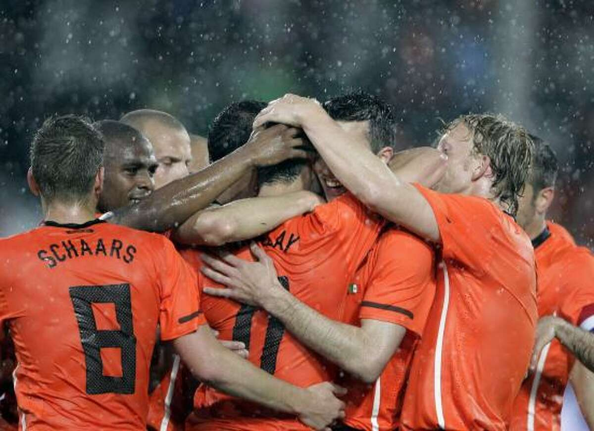 Netherland players react with fellow team member Robin van Persie, partially visible at center, after he scored a goal against Mexico in Freiburg, Germany,