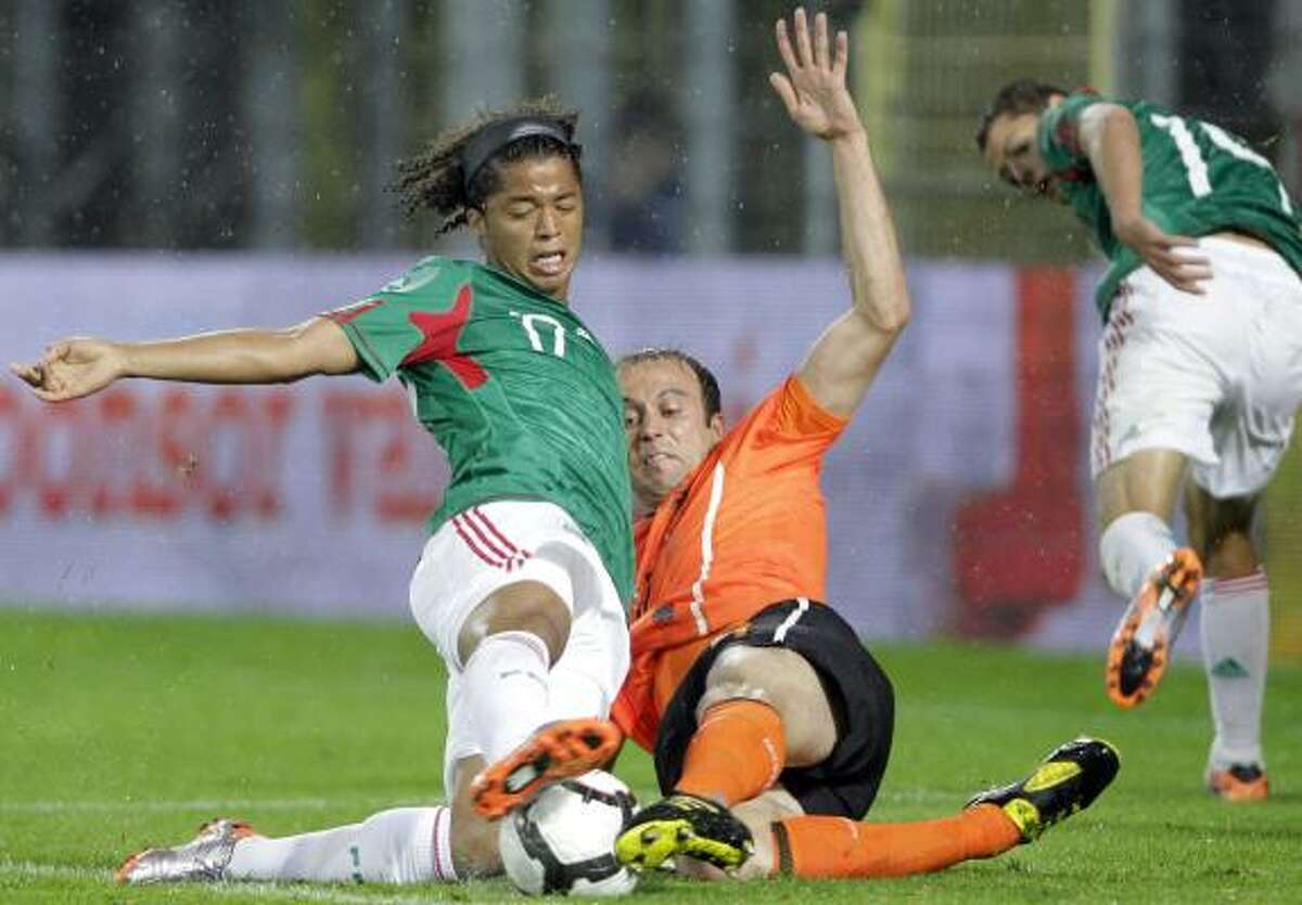 Netherland's Joris Mathijsen, front right, and Mexico's Giovani dos Sanstos, left, vie for the ball.