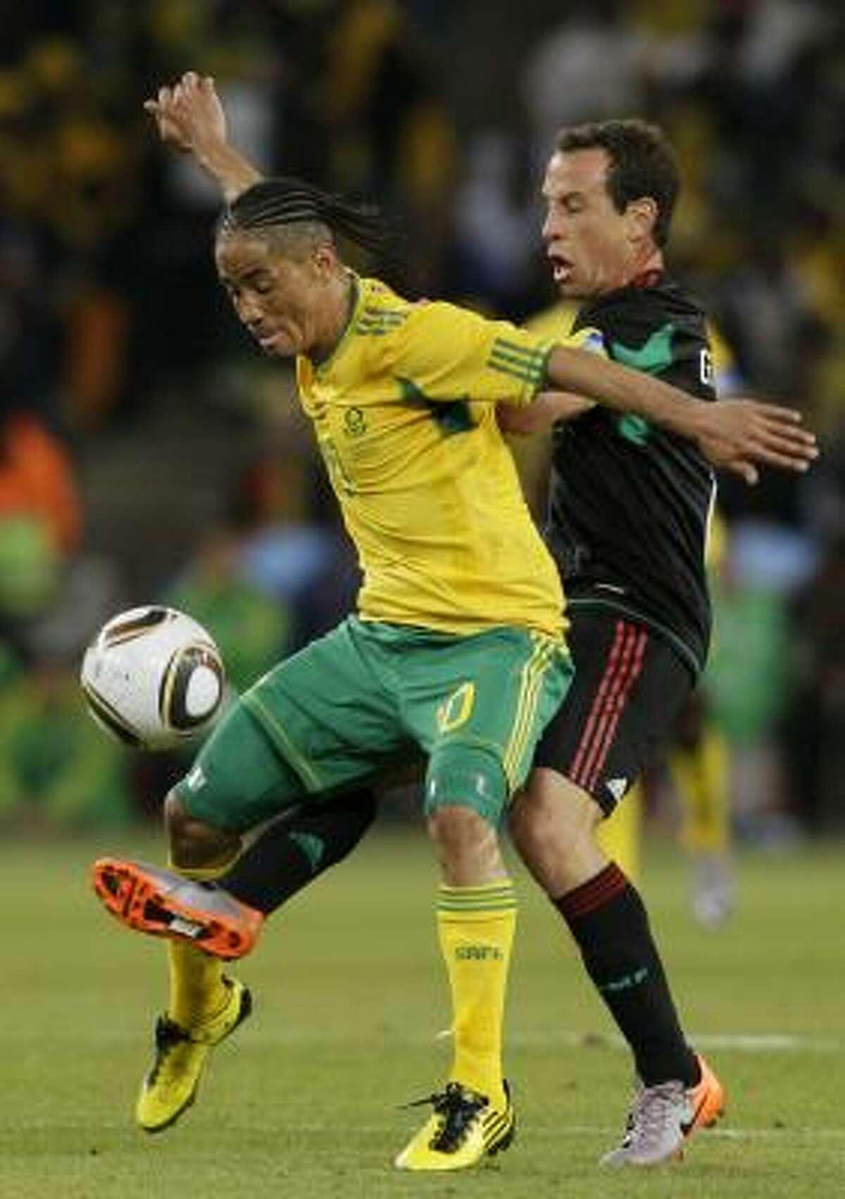 El sudafricano Steven Pienaar (izq.) resiste la marca del mexicano Gerardo Torrado.