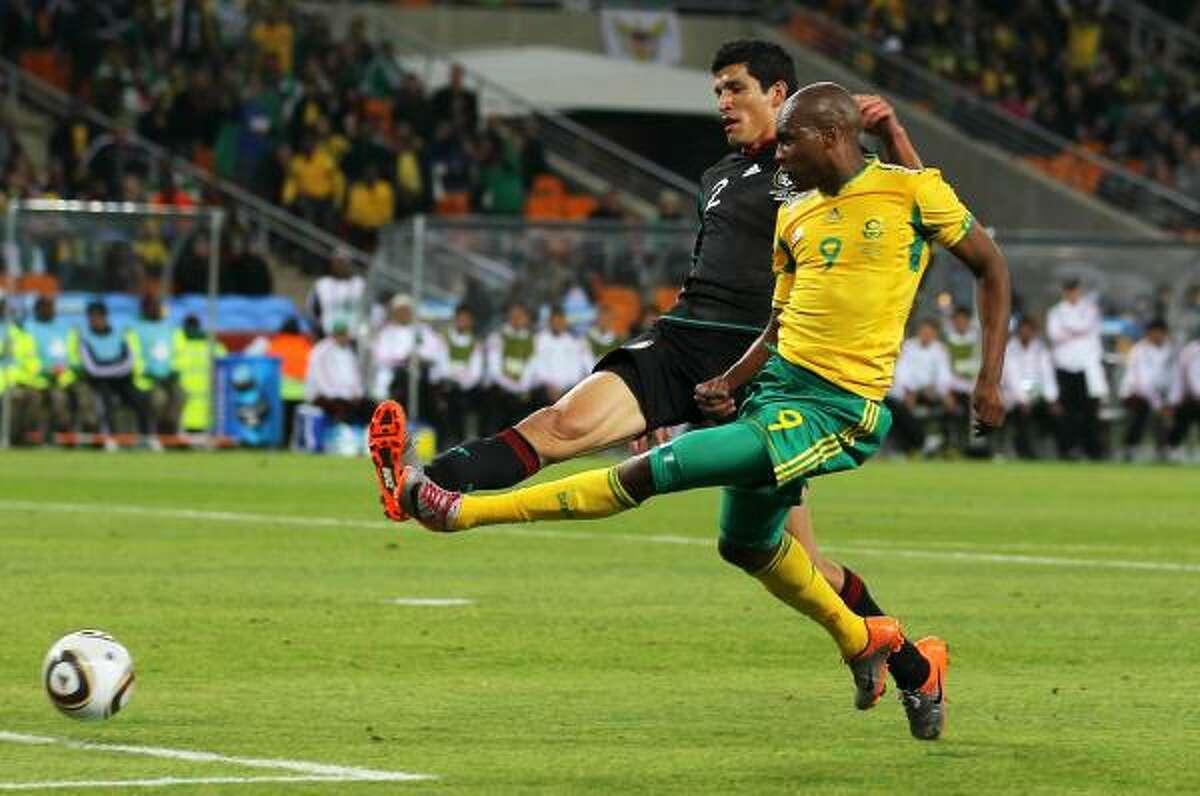 El sudafricano Katlego Mphela tira a gol ante la marca del defensa Francisco Rodríguez.