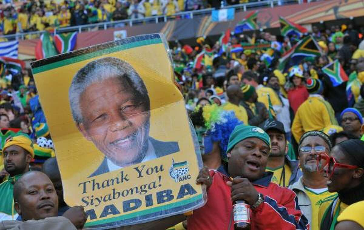 South Africa supporters hold a portrait of South Africa's former President Nelson Mandela prior to kickoff. Mandela's own World Cup joy was tempered, however, after his 13-year-old great-granddaughter Zenani died in a car crash on the way home from the World Cup kickoff concert in Soweto.