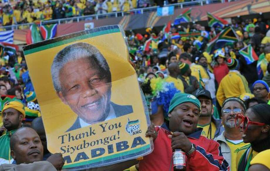 South Africa supporters hold a portrait of South Africa's former President Nelson Mandela prior to kickoff. Mandela's own World Cup joy was tempered, however, after his 13-year-old great-granddaughter Zenani died in a car crash on the way home from the World Cup kickoff concert in Soweto. Photo: ALEXANDER JOE, AFP/Getty Images